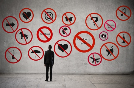 prohibitions: Young businessman standing in front of many prohibitions Stock Photo