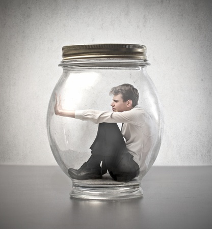 trap: Young businessman trapped in a glass jar