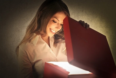 Smiling beautiful woman opening a gift photo