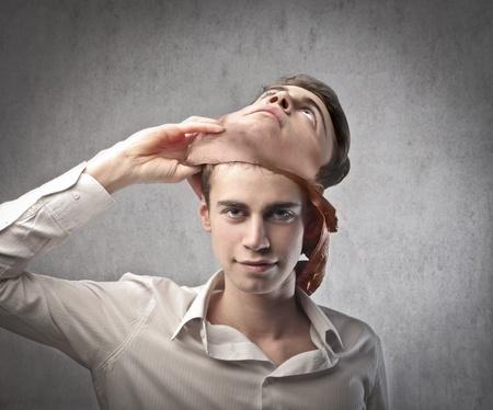 hipocresía: Hombre joven y sonriente quitarse una m�scara Foto de archivo