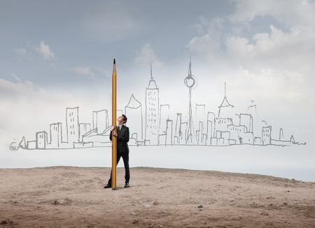 success concept: Young businessman holding a big pencil with hand-drawn cityscape in the background Stock Photo