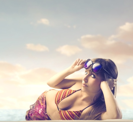 Beautiful woman lying on a beach and sunbathing Stock Photo - 13157848