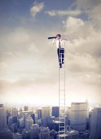 fernrohr: Junger Geschäftsmann auf einer Leiter über einer Großstadt mit Fernglas