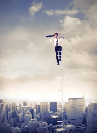 podnikatel: Mladý podnikatel na žebříku přes velkoměsta pomocí dalekohledu Reklamní fotografie