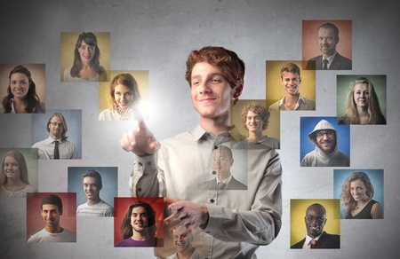 Smiling young man touching icons of different people on a touchscreen Stock Photo