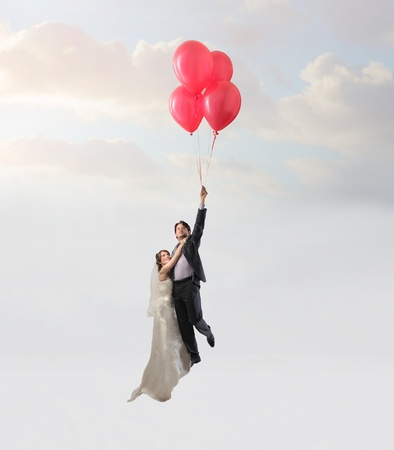 some: Happy married couple flying with some balloons