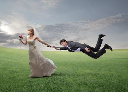 �crazy: Moglie felice in esecuzione su un prato verde e tirando il marito per un braccio Archivio Fotografico