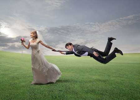 gente loca: Mujer feliz corriendo en un prado verde y tirando de su marido por el brazo