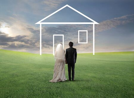 Married couple walking on a green meadow towards the shape of a house Stock Photo - 13361071