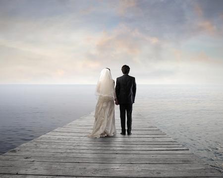 pareja de esposos: Pareja casada de pie en un muelle sobre el mar