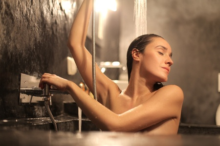 lying in bathtub: Beautiful woman having a shower in a bathtub
