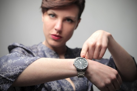 delay: Beautiful woman showing the time on her wristwatch