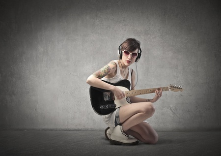 earbud: Beautiful woman with a tattoo on her arm playing the guitar