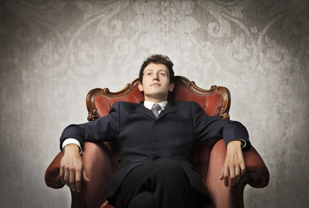 riches adult: Young businessman relaxing on an armchair