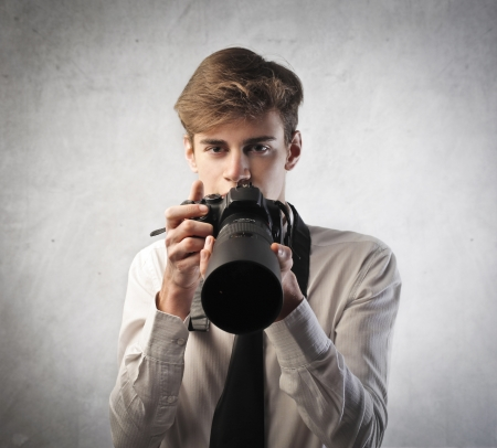 reflex: Young photographer holding a camera