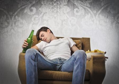 jovenes tomando alcohol: Joven durmiendo en un sillón y sosteniendo una botella de cerveza y un plato de patatas fritas