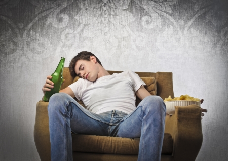 Young man sleeping on an armchair and holding a beer bottle and a bowl of chips photo