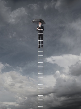 high scale: Young businessman on a ladder holding an umbrella with stormy sky in the background Stock Photo