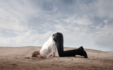 inhibition: Young businessman burying his head in the sand