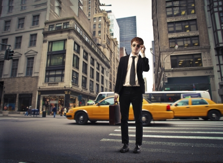 delay: Young businessman on the street of a big city