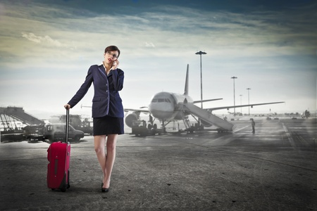 Young businesswoman at the airport talking on the mobile phone and holding a trolley case photo