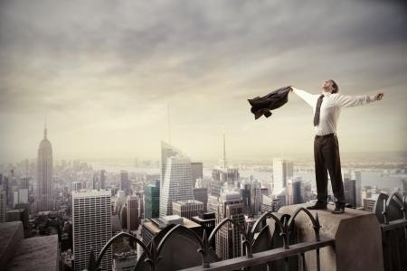 Joven hombre de negocios extendiendo sus brazos mientras está de pie en un skscraper en una gran ciudad