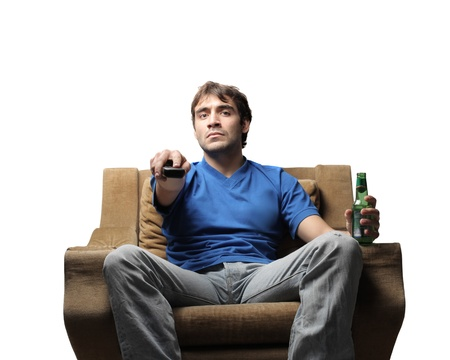 tedium: Man sitting on an armchair and zapping with a beer in his other hand Stock Photo