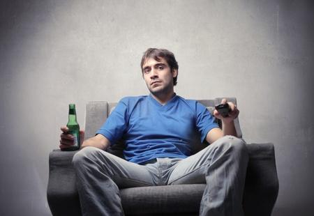 ver tv: El hombre joven sentado en un sillón con una cerveza en sus manos