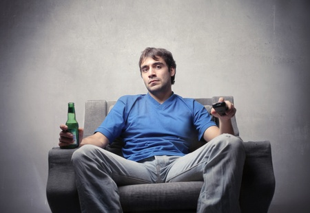 tedium: Young man sitting on an armchair with a beer in his hands Stock Photo