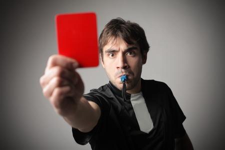 Enojado árbitro silbando y mostrando una tarjeta roja
