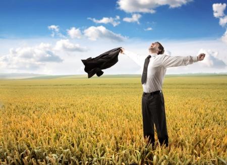 幸せな実業家彼の腕を伸ばし、麦畑に息を吐く