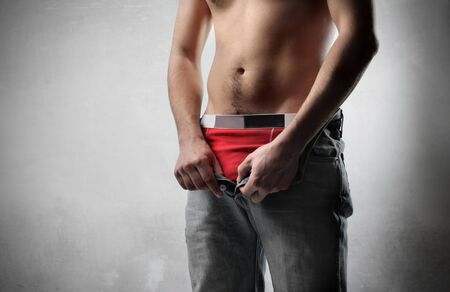 man in underwear: Young man taking off his blue jeans Stock Photo