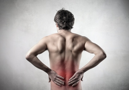 man back pain: Rear view of a bare-chested man suffering from backache Stock Photo