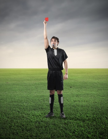 Referee on a meadow raising a red card and whistling