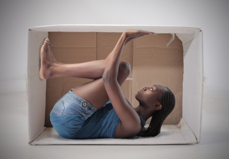 Young african woman imprisoned in a carton Stock Photo - 13659338