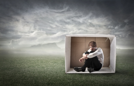 Sad young businessman sitting in a carton on a green meadow under stormy sky photo