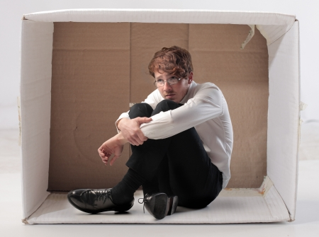 Sad young businessman sitting in a carton photo