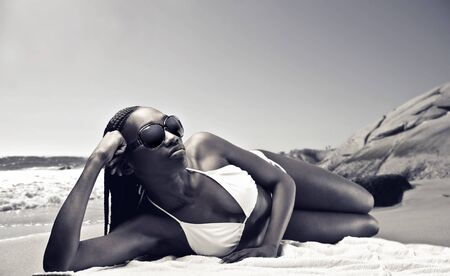 Beautiful african woman sunbathing on a beach photo