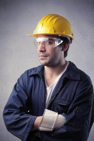 operative: Portrait of a worker wearing a blue working suit and a security cap