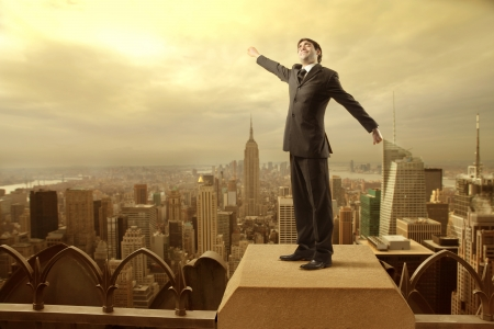 awakening: Businessman on a skyscraper stretching out his arms with big city in the background