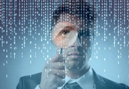 loupe: Jeune homme d'affaires zoom sur un code binaire sur un moniteur avec une loupe