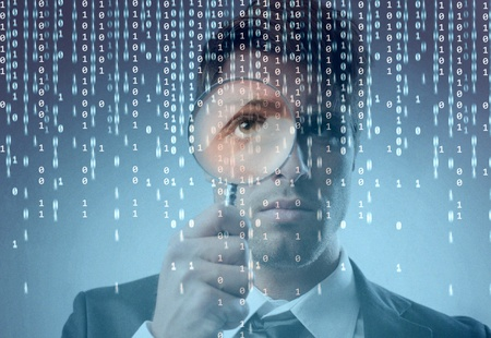 inspection: Young businessman zooming on a binary code on a monitor with a magnifying glass