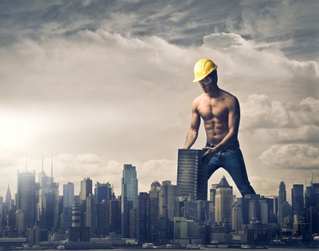 power giant: Young brawny worker settling a skyscraper in the skyline of a big city Stock Photo