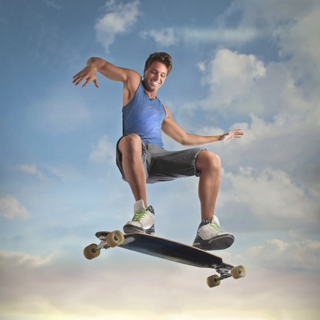 enables: Smiling young man skateboarding with sky in the background