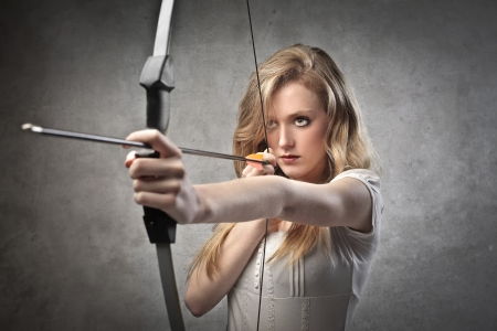Beautiful young woman drawing a bow