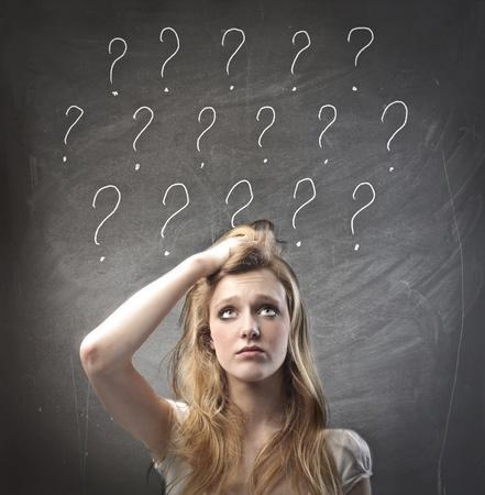 Jonge vrouw met twijfelachtige uitdrukking en vraagtekens over haar hoofd