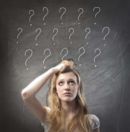 Young woman with doubtful expression and question marks over her head photo