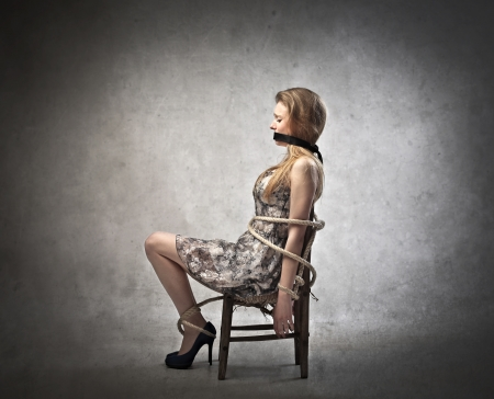 gagged: Sad scared young woman tied tight to a chair