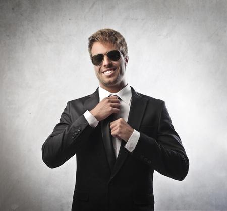 homem: Young businessman adjusting his necktie