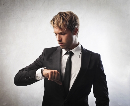 Young businessman looking at his wristwatch photo